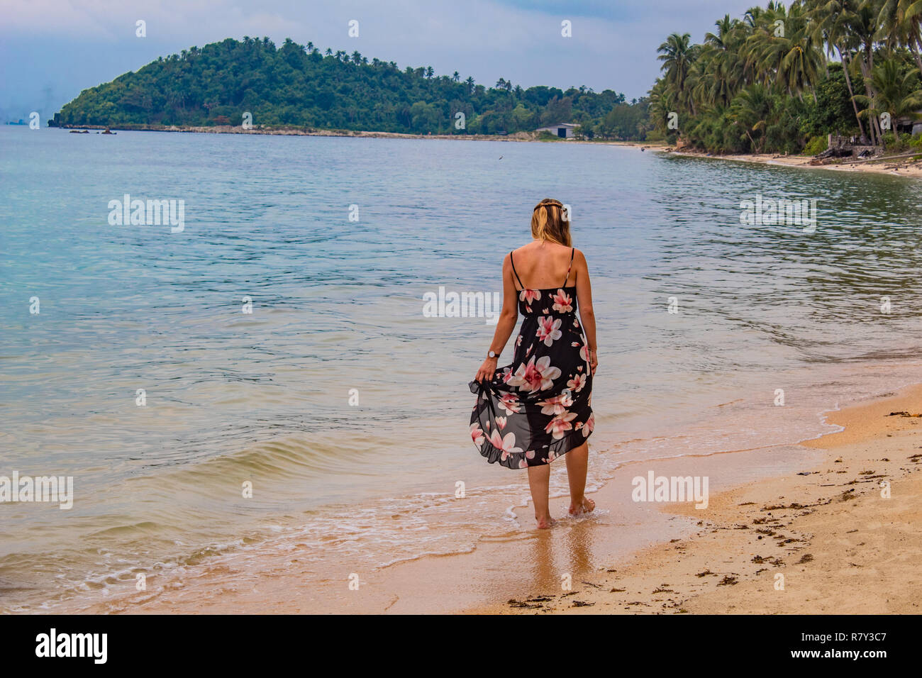 Backview of Woman with long sundress walking on the beach - Stock Image