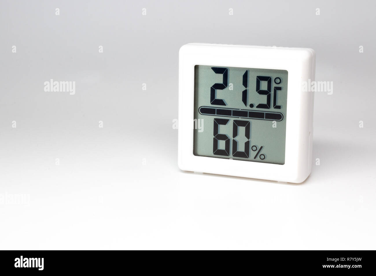 Digital device measuring temperature and humidity. Thermometer and hygrometer. Celsius and percent. - Stock Image