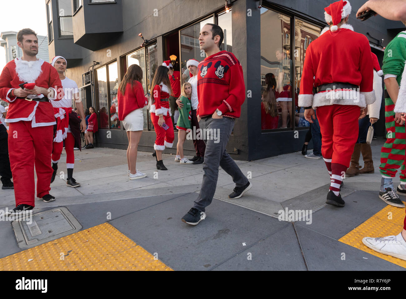 Holiday revelers in San Francisco dressed in Santa Claus/Christmas costumes for the annual SantaCon pub crawl. - Stock Image