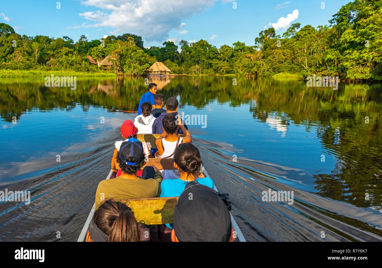 Transport in canoe along the rivers of the Amazon River Basin inside the Yasuni National Park with a view of a lodge in traditional style, Ecuador. - Stock Image