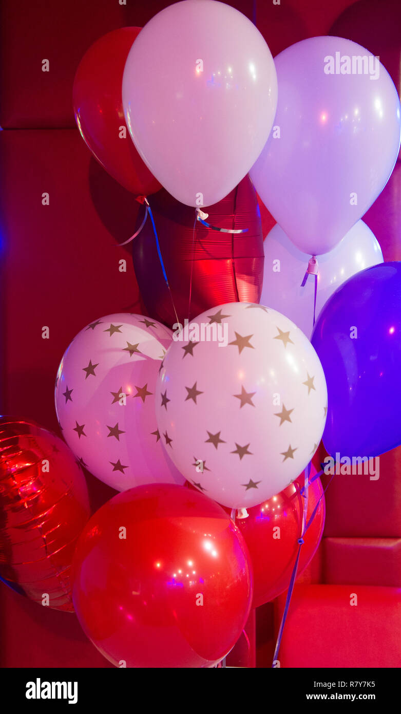 Balloon traditional holiday attribute. Every party needs balloons. Happy birthday concept. Celebrate birthday holiday with festive colorful air balloons. Red and white balloons with stars pattern. - Stock Image