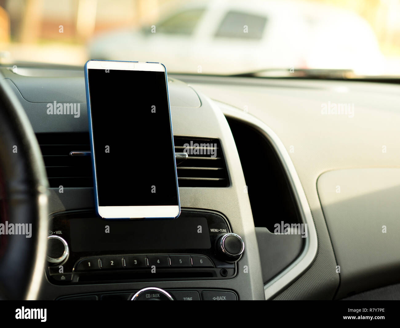 mobile phone located in the center of the vehicle console. Black screen phone in the car - Stock Image