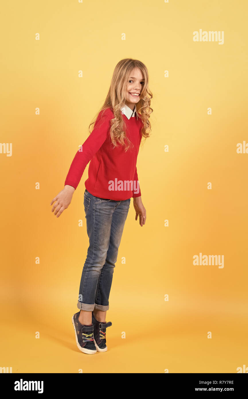 Girl in red sweater and jeans stand on tiptoe. Child smile with curly blond hair on orange background. Beauty, look, hairstyle. Kid fashion and style. Happy childhood concept. - Stock Image