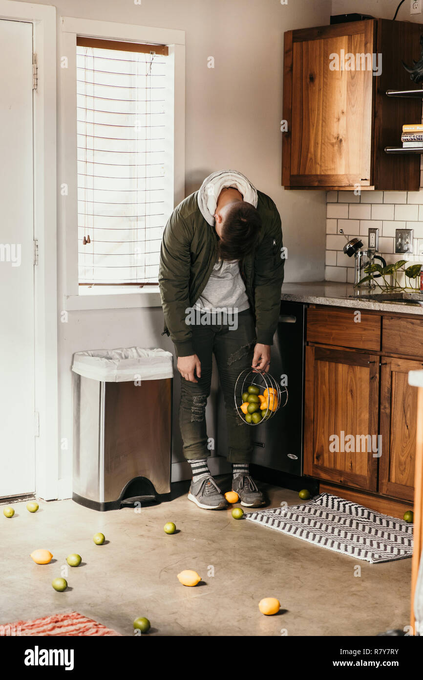 Upset and Defeated Young Adult Person Accidentally Spills Basket of Lemons and Lime Fruit All Over Modern Home Kitchen Floor and has a Sad Emotion - Stock Image