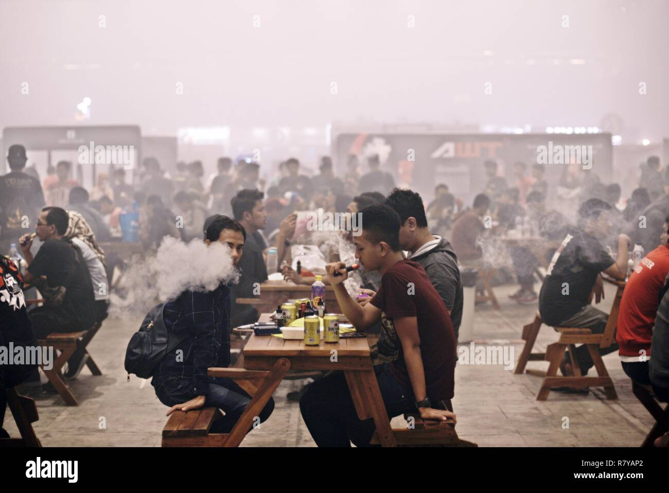 Visitors puff on their e-cigarettes after having meals during the 2018 Vape Fair at Jakarta International Expo, Jakarta, Indonesia. © Reynold Sumayku - Stock Image