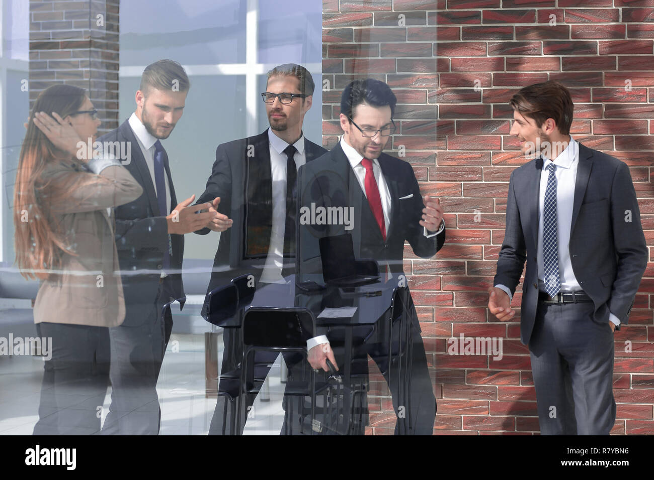 people standing in modern office behind glass wall - Stock Image
