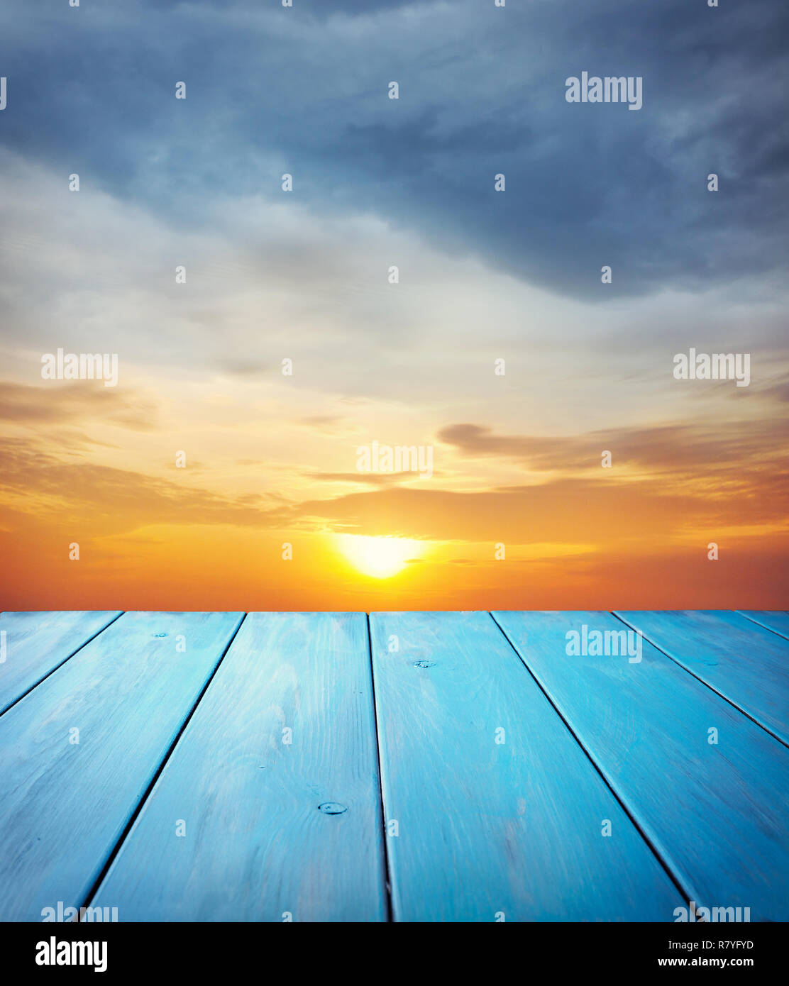 Blue wooden table at orange sunset sky background - Stock Image
