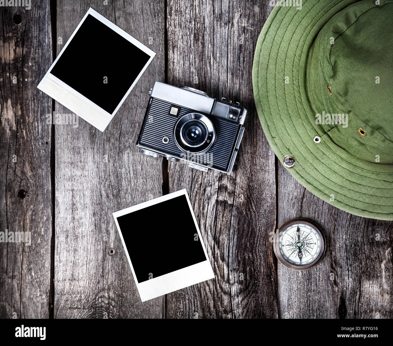 Old film camera, photos with space for pictures, hat and compass on the wooden background - Stock Image