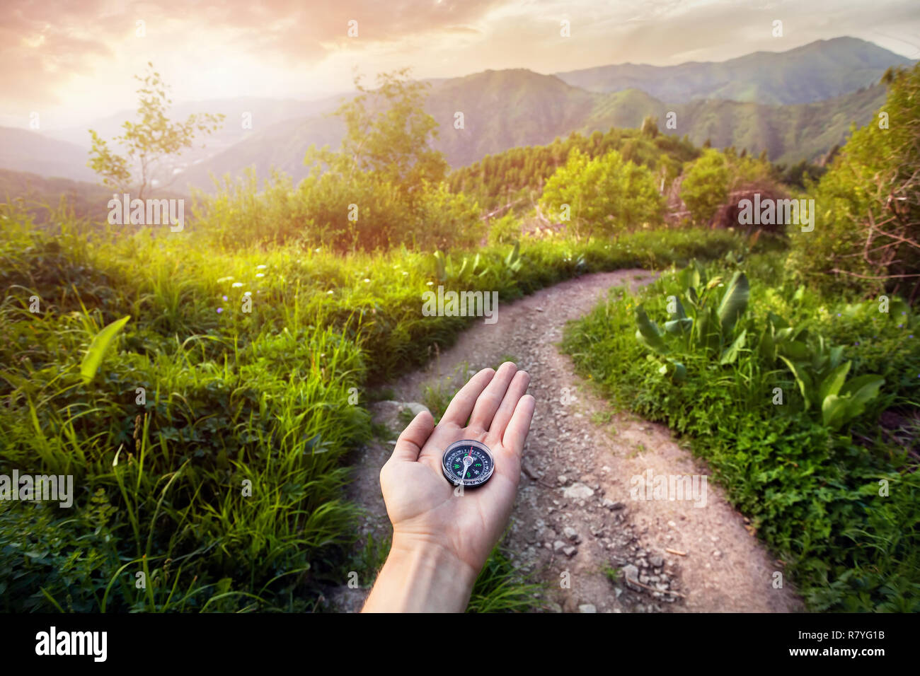Hand with compass at mountain road at sunset sky in Kazakhstan, central Asia - Stock Image