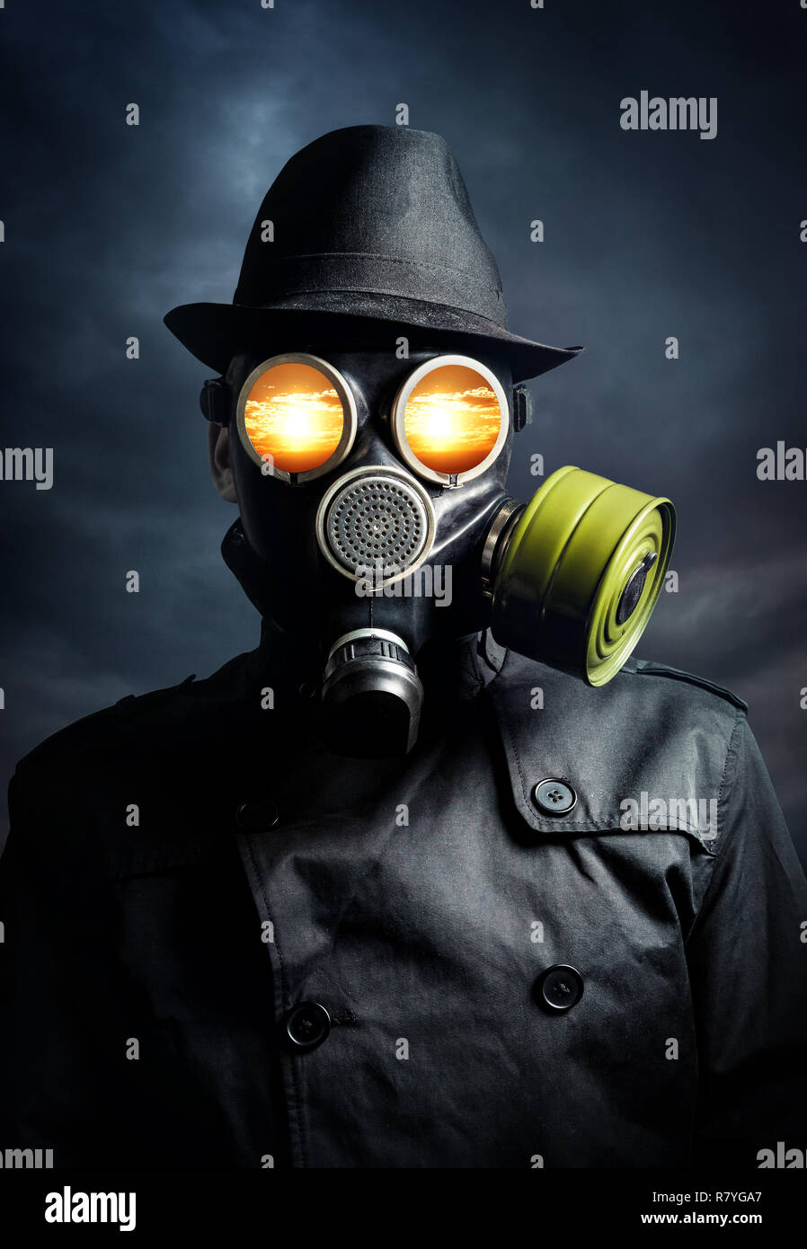 Man in gas mask with explosion in his eyes at dark sky background - Stock Image