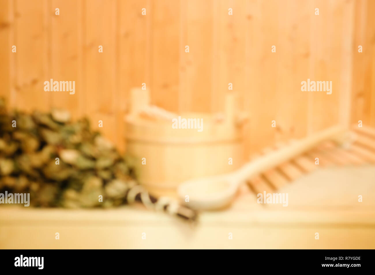 Blurred background of wooden bucket, a birch broom and other accessories in a finnish classic sauna or russian bath. Free space on a wooden wall - Stock Image