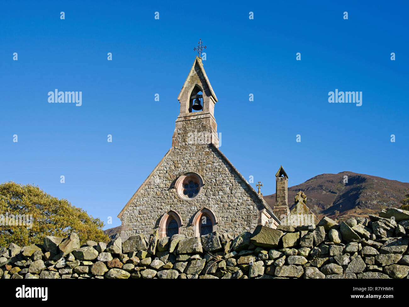 Bell tower and stone-built gable wall of St Bega's Church, Bassenthwaite, seen against deep blue sky, dry stone wall in foreground, Lake District UK. - Stock Image