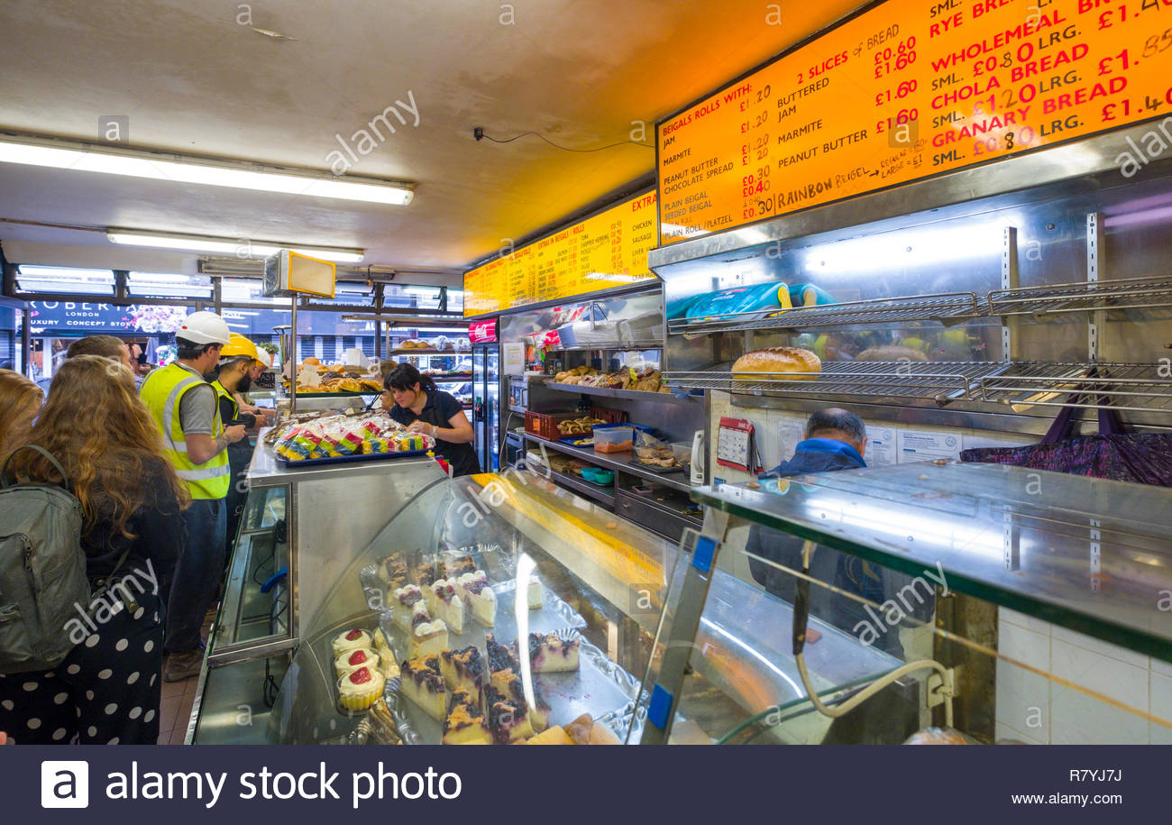 Construction workers wearing hardhats and high visibility vest ordering a late breakfast inside the Beigel Shop, Brick Lane, Tower Hamlets, London, En - Stock Image