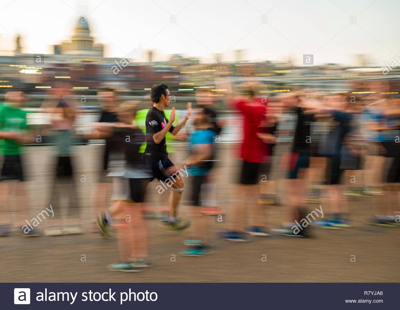Male runner getting high-fives as she runs a friendly gauntlet of fellow runners, South Bank, Southwark, London, England, United Kingdom - Stock Image