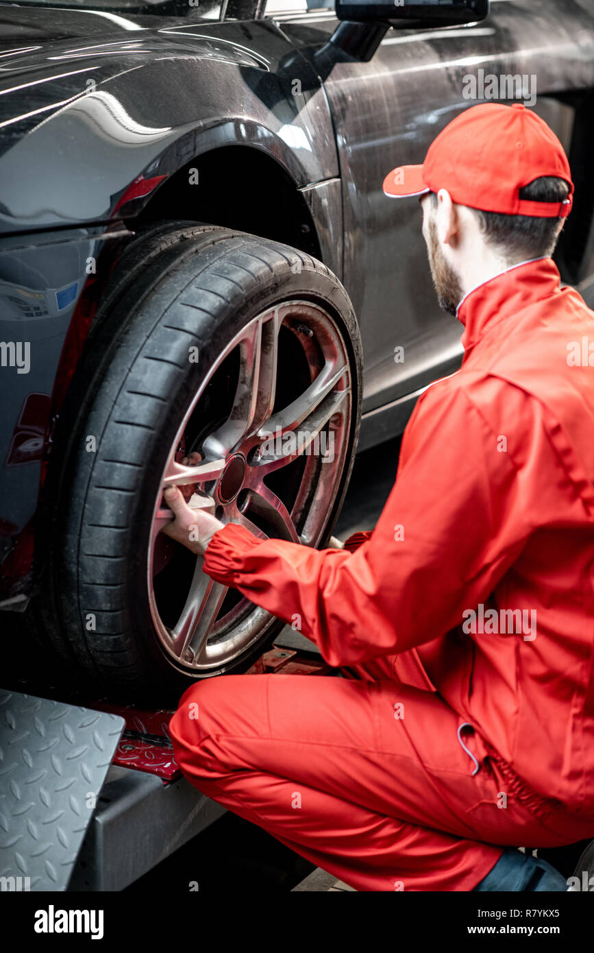 Car Service Worker In Red Uniform Changing Wheel Of A Sport Car At