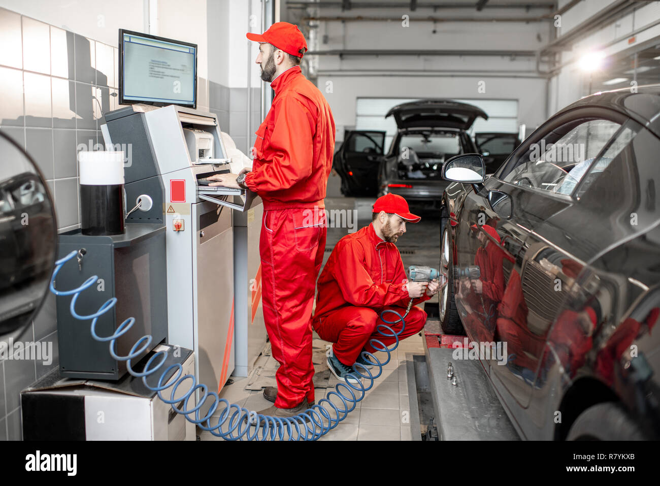 Car Service Workers In Red Uniform Balancing And Changing Wheels Of