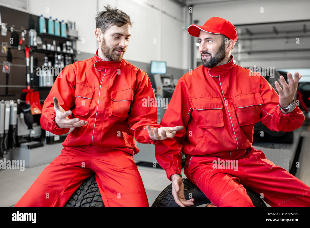 Car Service Workers In Red Uniform Having A Break Sitting Together