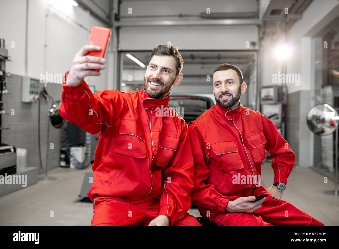 Car Service Workers In Red Uniform Making Selfie Photo With Phone