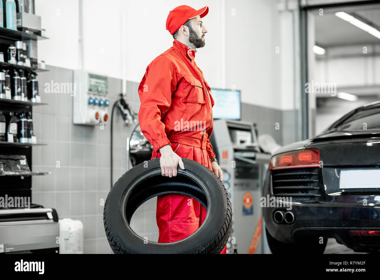 Car Service Worker In Red Uniform Carrying New Tires At The Tire