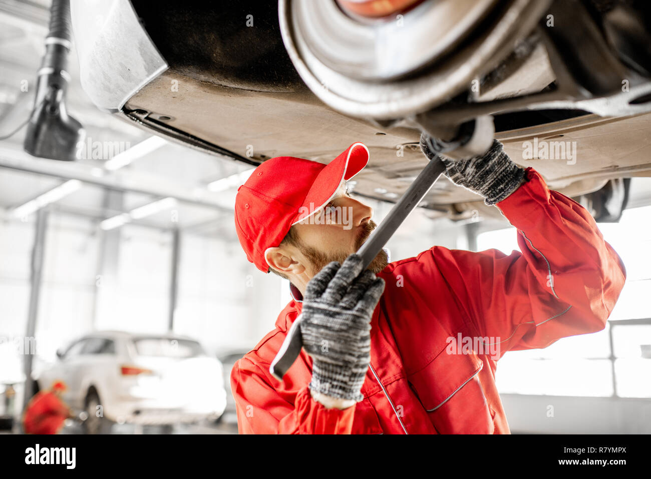 Auto mechanic in red uniform diagnosing car on the hoist at the car service - Stock Image