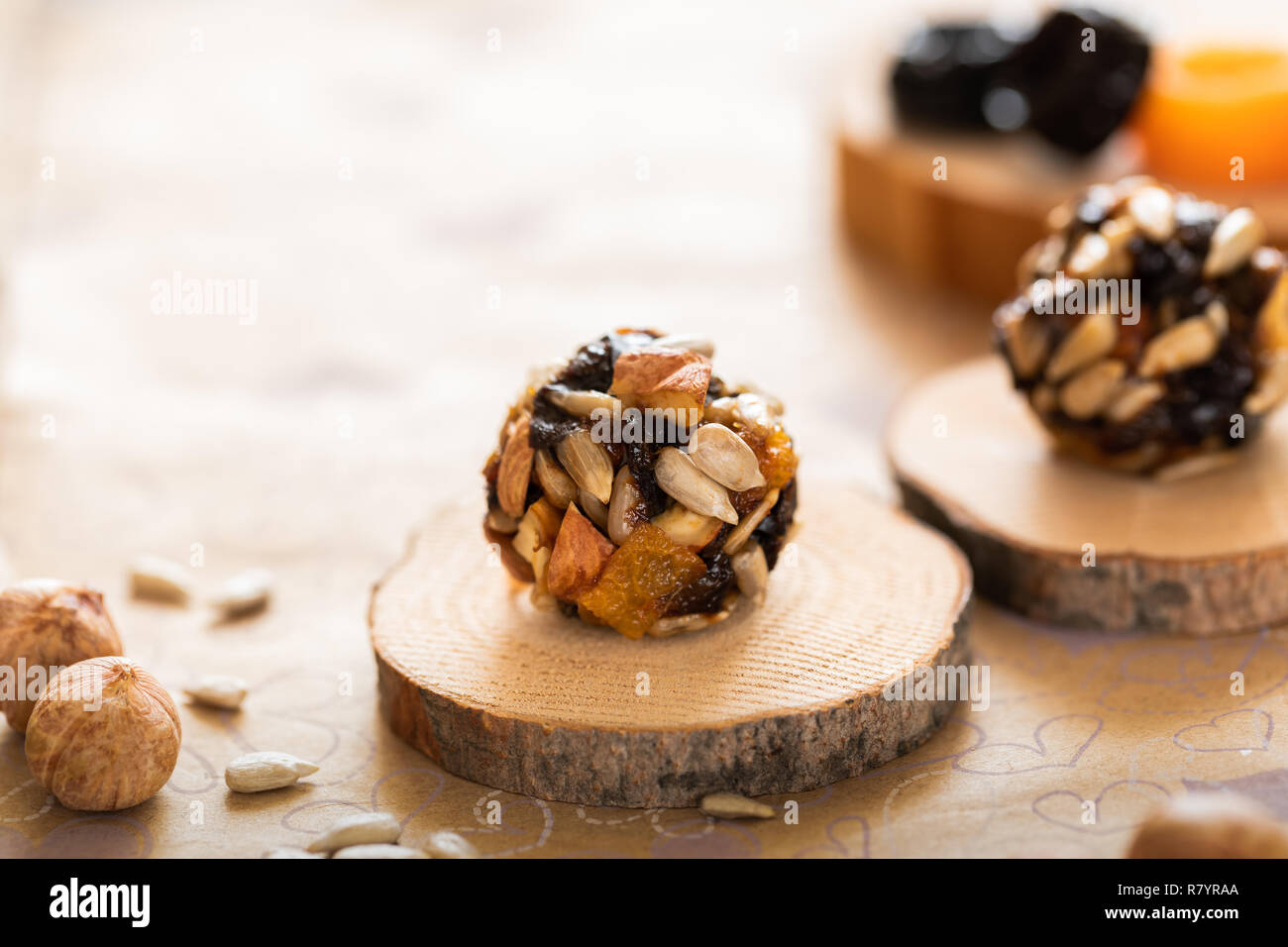 Handmade energy balls on wooden saw cuts and ingredients for their preparation on paper background. Stock Photo