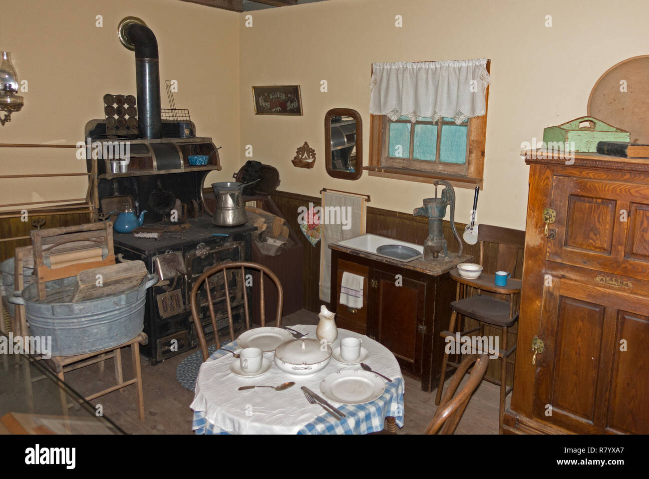 Historical kitchen with wood burning stove, clothes wringer wash tub displayed at Otter Tail County Historical Museum. Fergus Falls Minnesota MN USA - Stock Image