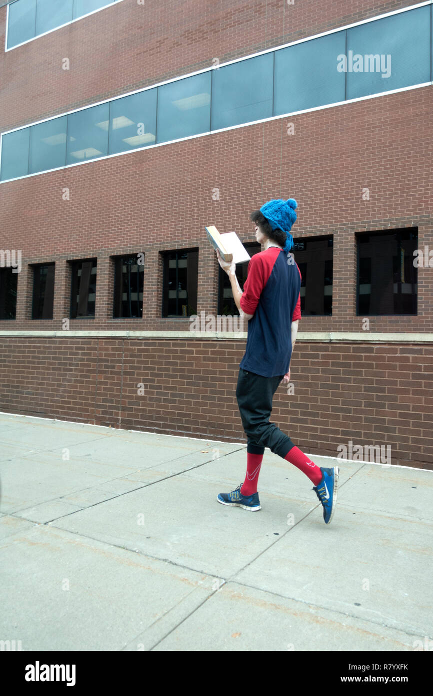 Lean student reading a book while taking a walk wearing very stylish clothing. St Paul Minnesota MN USA - Stock Image