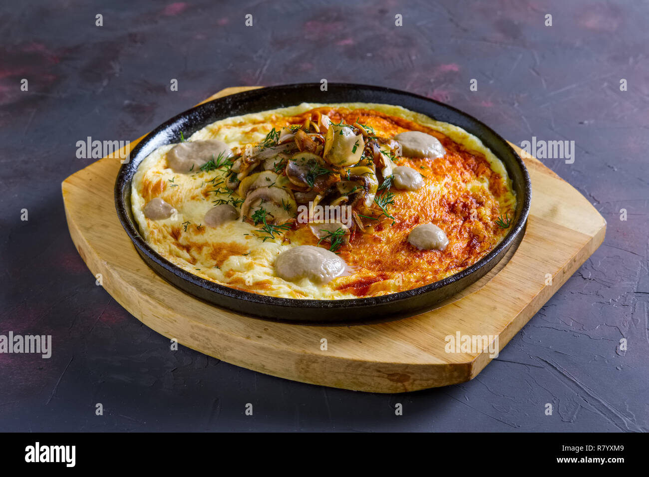 Vegetarian omelette with mushrooms in cast iron pan - Stock Image