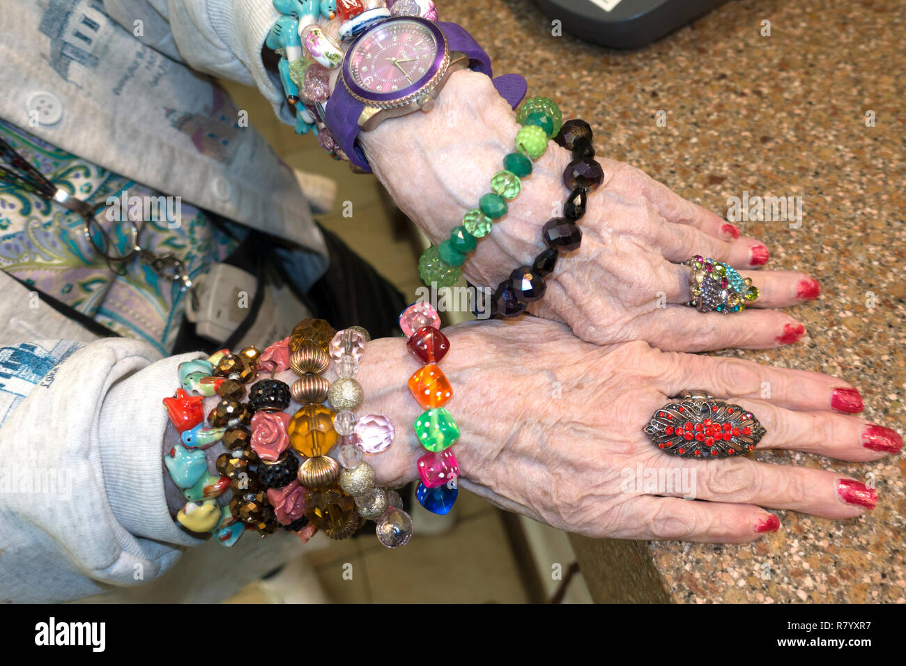 Elderly woman modeling the many gorgeous bracelets and jewelry that she made. Downers Grove Illinois IL USA - Stock Image