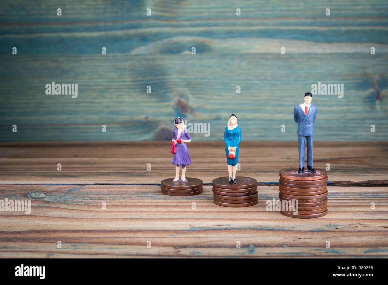 Miniature people standing on piles of coins - Stock Image