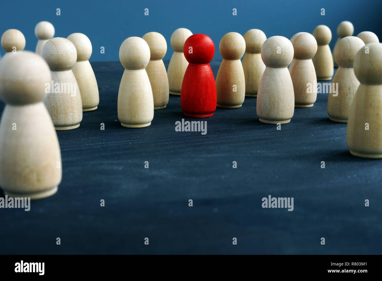 Wooden figures and one red figure. Be different. Stand out from the crowd. Stock Photo