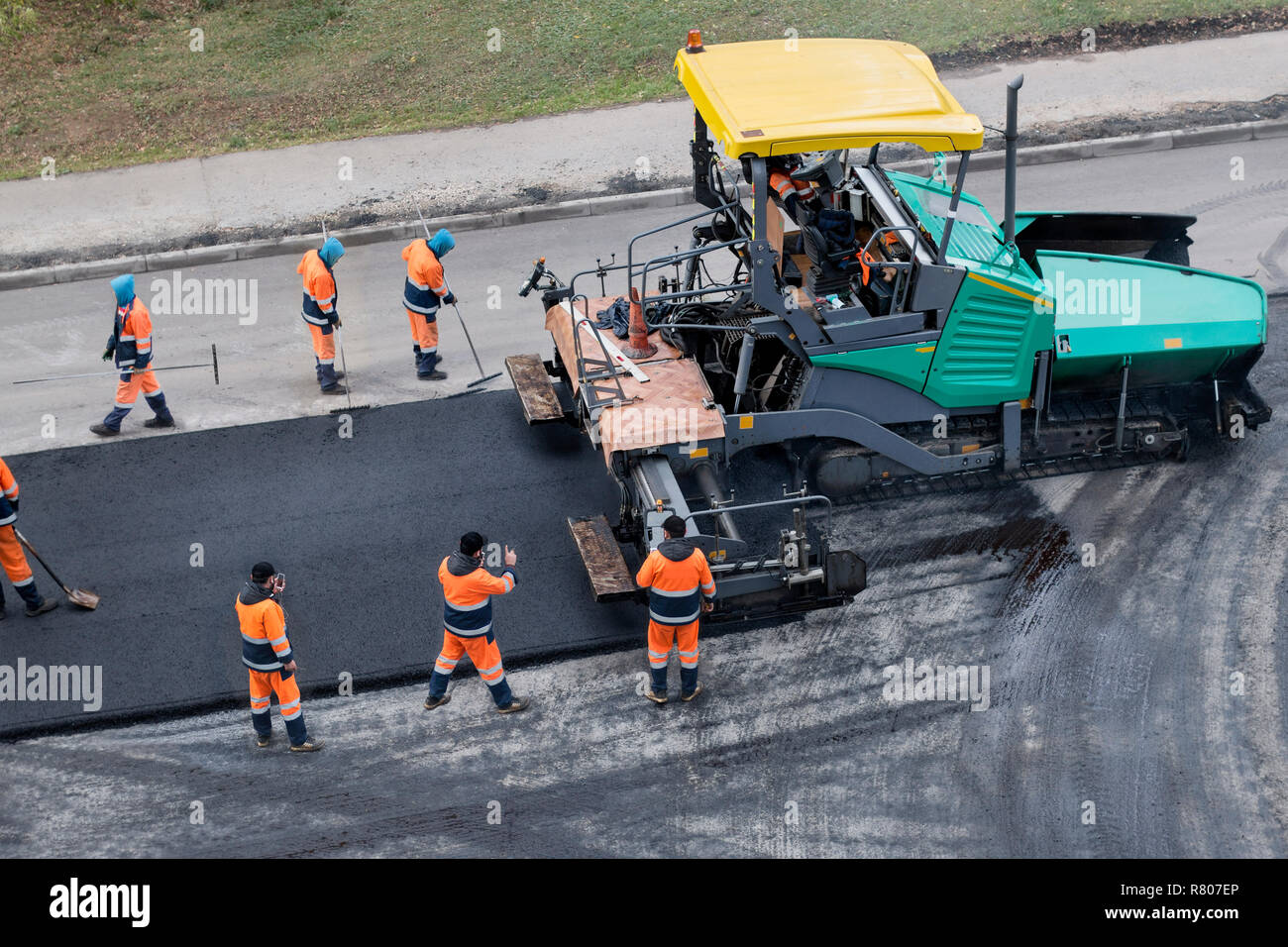 Asphalt paver machine or paver finisher places a layer of fresh asphalt. Road renewal process, construction working. Collage, unrecognizable workers. - Stock Image