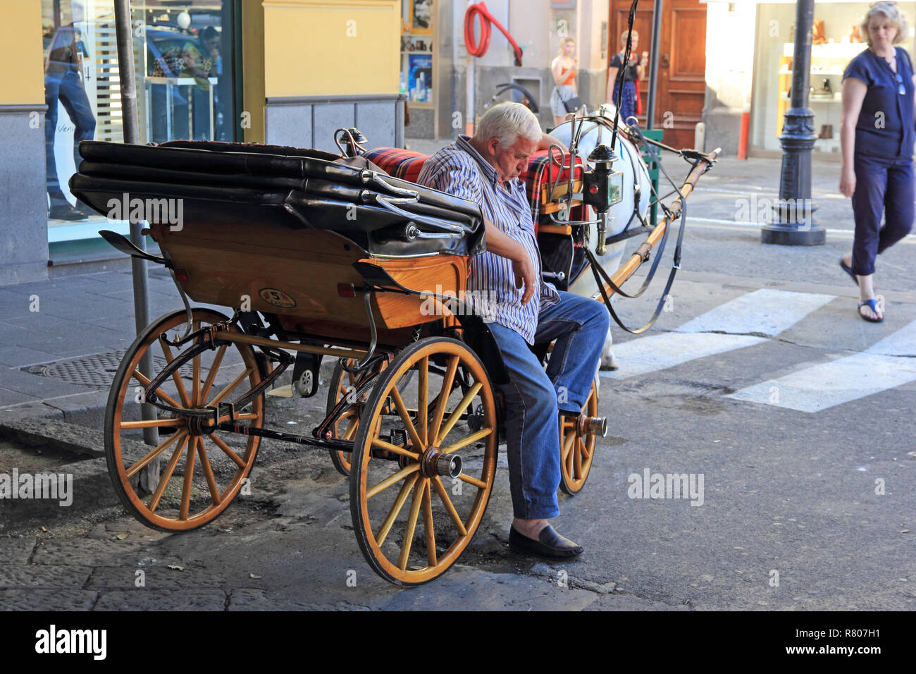 Carriage driver, snoozing in shady corner of Piazza Tasso, Sorrento - Stock Image
