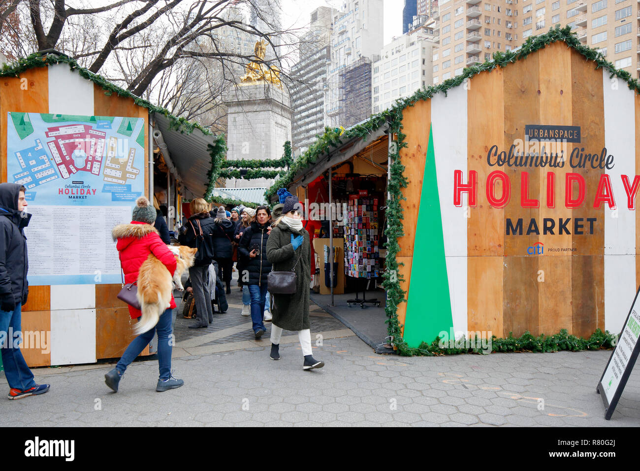 People near the entrance to Columbus Circle Holiday Market in Central Park with the Maine Monument in the background, New York City Stock Photo