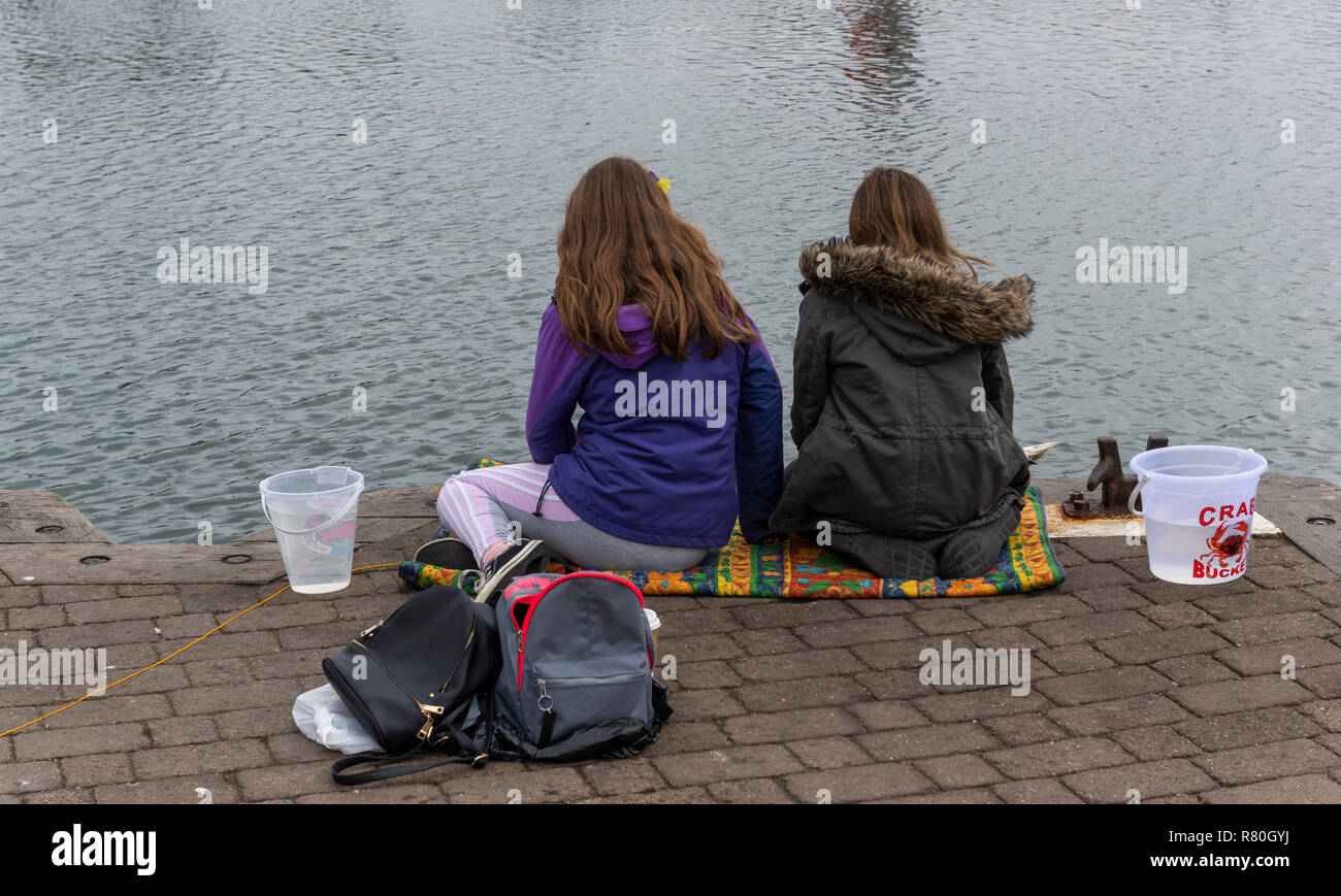 Lymington, England - October 25, 2018: Crab fishing by two girls in the harbor of Lymington with two small buckets and some bags. Stock Photo
