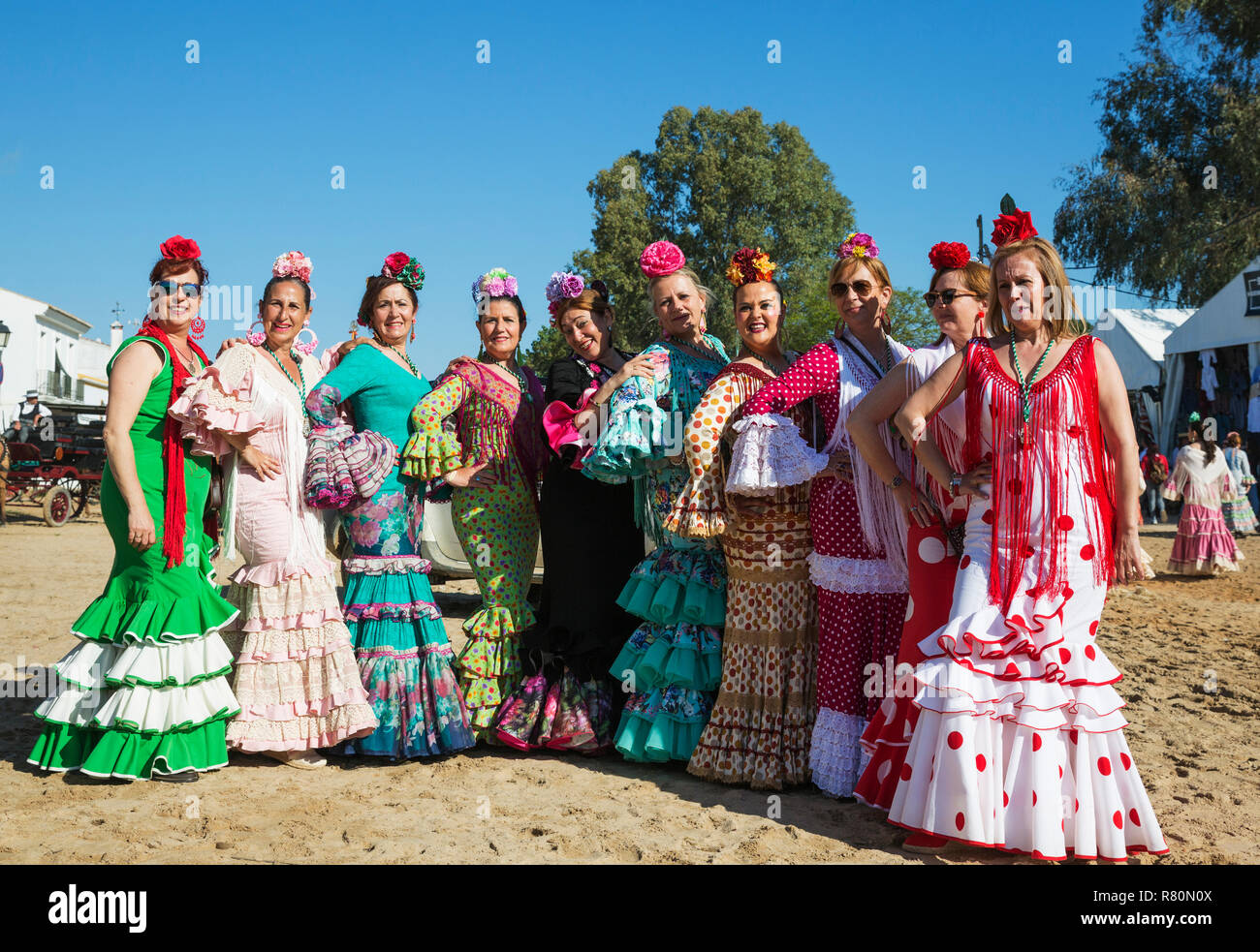 Women wearing beautifully coloured gypsy dresses during the annual Pentecost pilgrimage of El Rocio. Huelva province, Andalusia, Spain. - Stock Image