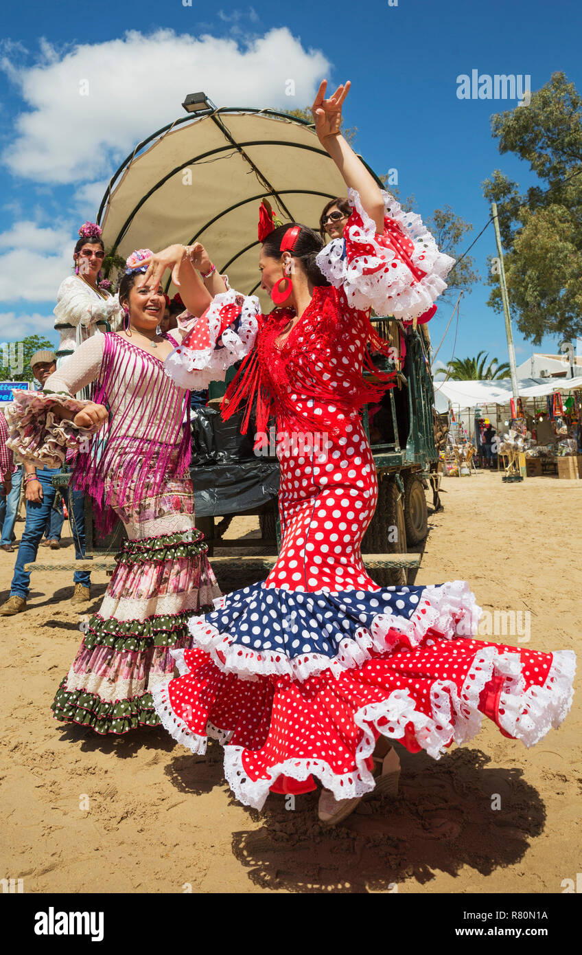 During the annual Pentecost pilgrimage of El Rocio the women wear beautifully coloured gypsy dresses and readily dance the Sevillana. Huelva province, Andalusia, Spain. - Stock Image