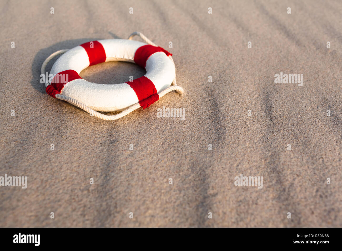 2af29b6f69d Nostalgic miniature white life buoy with rope and red stripes at wavy beach  sand background (