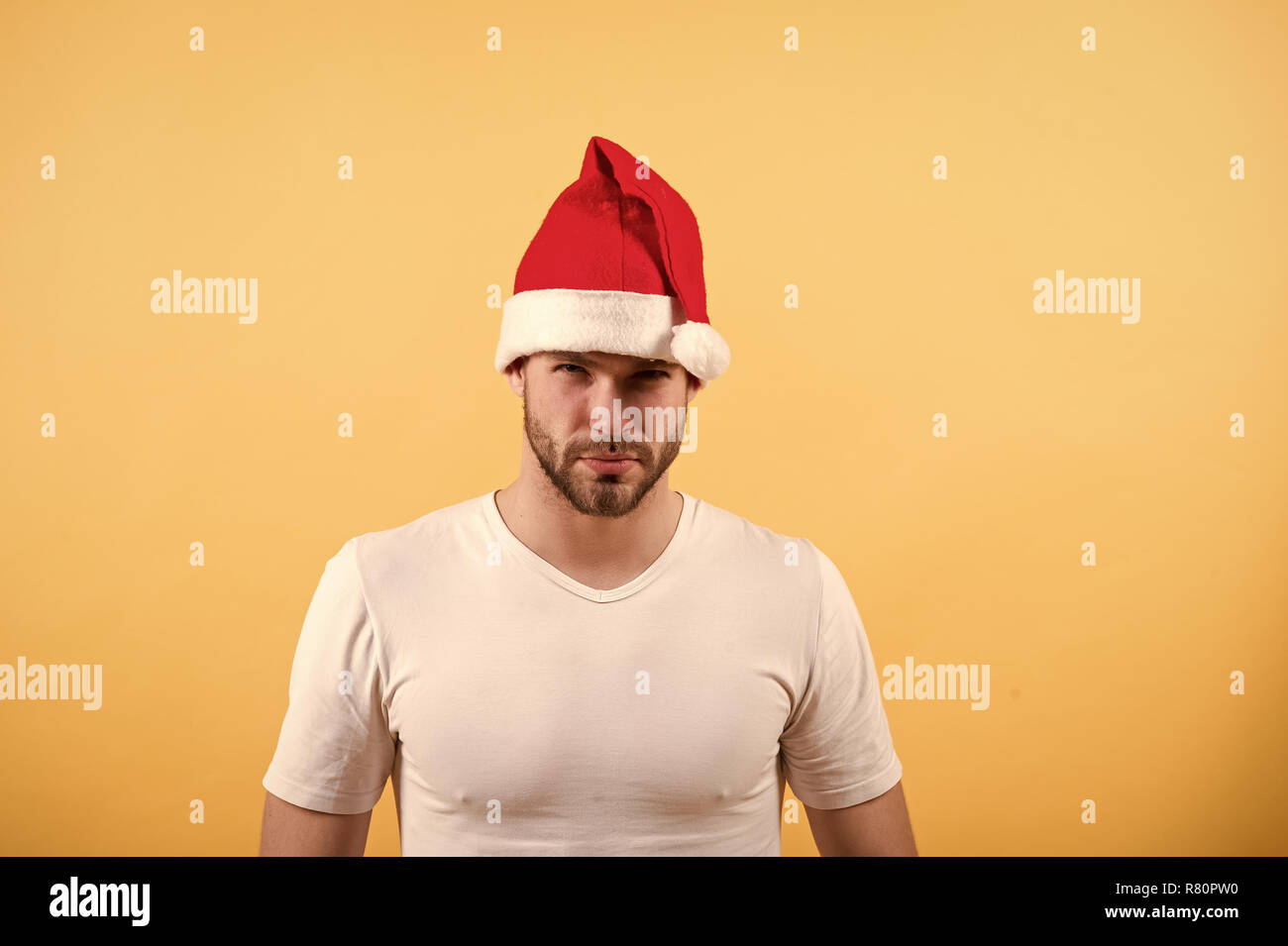 ba9f4ba3b2715 Santa claus fashion. Man santa in white tshirt on orange background.  Christmas and new year party. Macho with bearded face in red xmas hat.