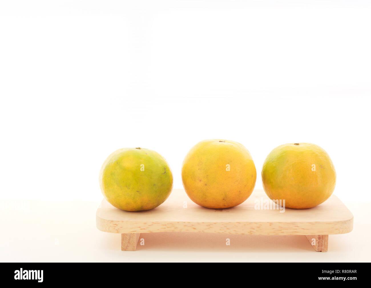 fresh ripe green and orange tangerine (citrus, mandarin) oranges, fruit on wood tray isolated on white table background. Seasonal Tropical Fruit, Natu - Stock Image