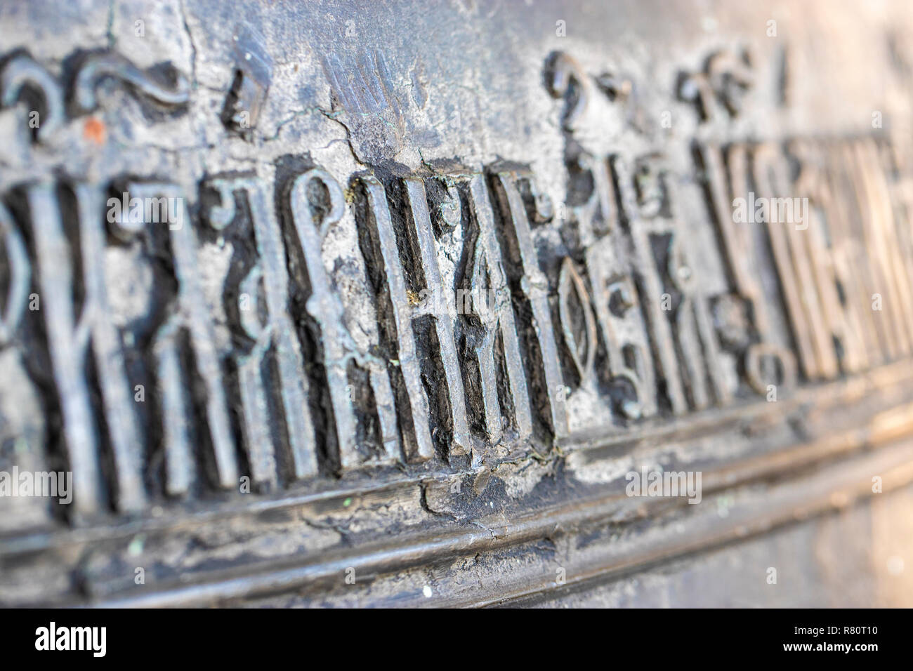 Close-up of ancient Slavic letters on ancient bronze bell in orthodox church in Rostov the Great - Stock Image