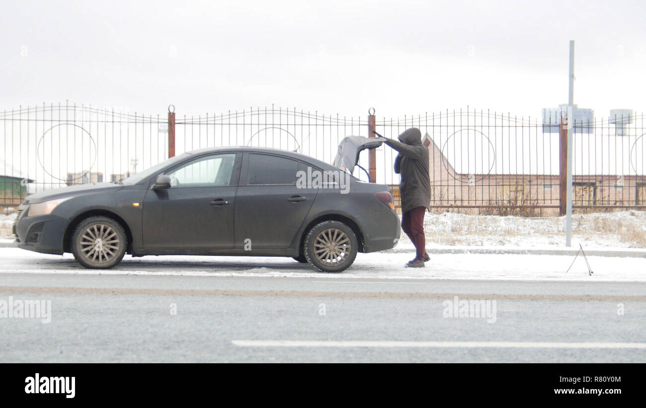 A car accident. A young man standing by a broken car. Opening the trunk - Stock Image