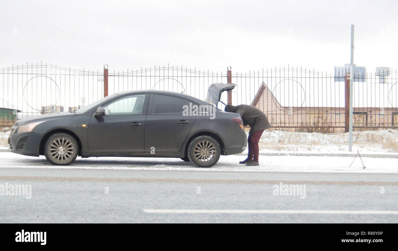 A car accident. A young man standing by a broken car. Looking into the trunk - Stock Image