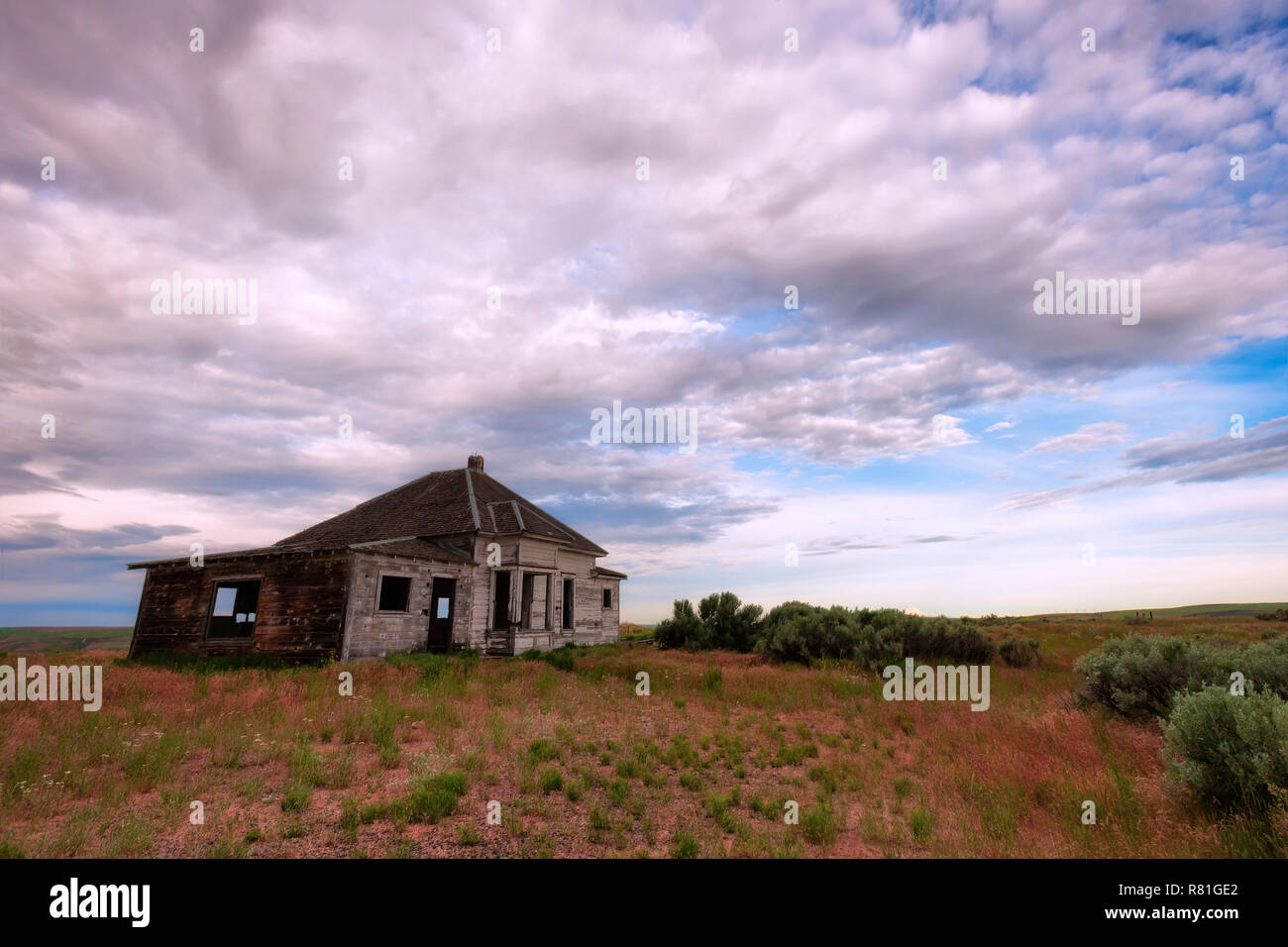 A shell of an abandoned home sits in a high desert landscape dotted with sagebrush under stormy skies. - Stock Image