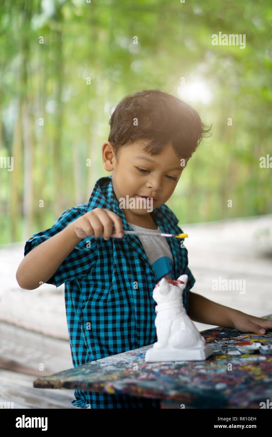 Asian kids enjoying his painting with paintbrush. - Stock Image