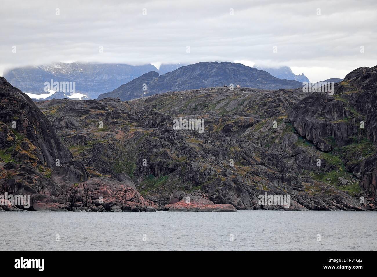 Grönland Christian Sund: karge Felsen, glatt geschliffen,  mit dünner Vegetation, rotes Gestein - Stock Image