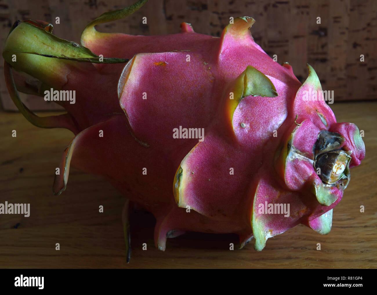 sweet pitaya fruit, pink-skinned ripe pitahaya fruit also called hylocereus undatus on wooden table - Stock Image