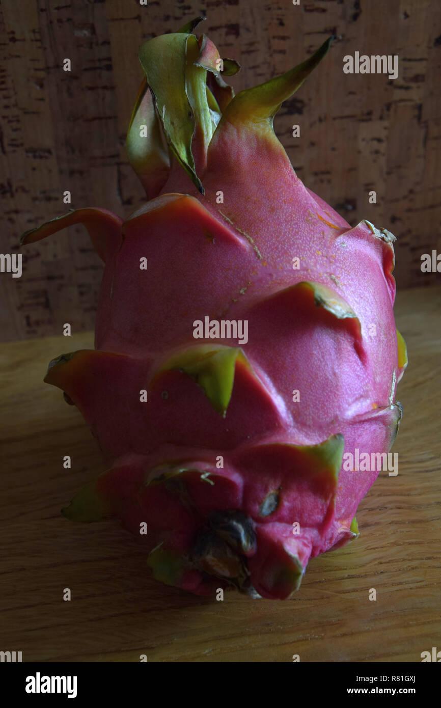 ripe dragon fruit, pink-skinned ripe pitahaya fruit also called hylocereus undatus on wooden table - Stock Image