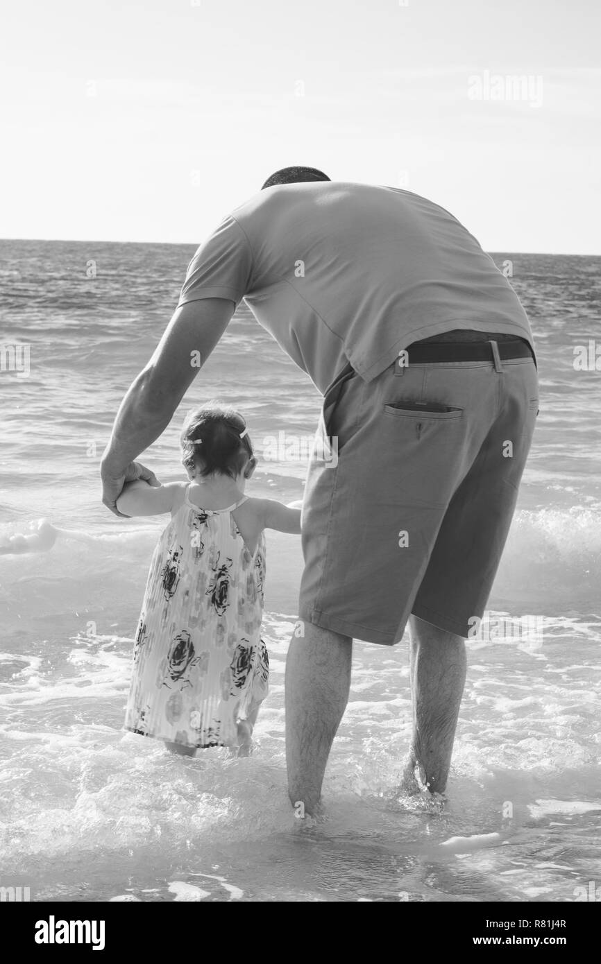 Father and Young Toddler Daughter Playing in the Shallow Beach Water on Travel Vacation in Black and White - Stock Image