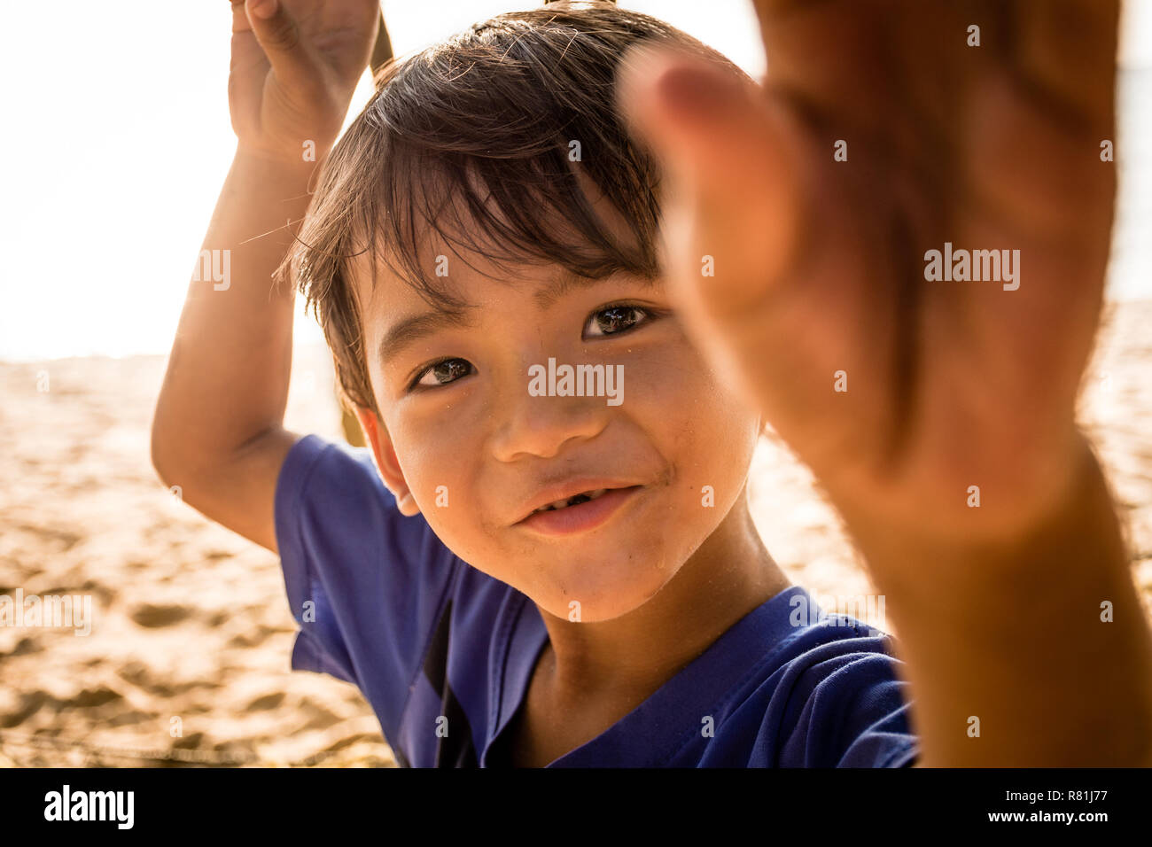 A young local boy from Cambodia, playfully looking at and grabbing at the camera. - Stock Image